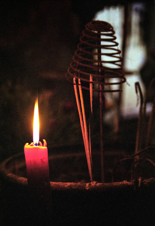Incense sticks burn by candle light in a Chinese temple in Hô Chi Minh City (Saigon), 2003.