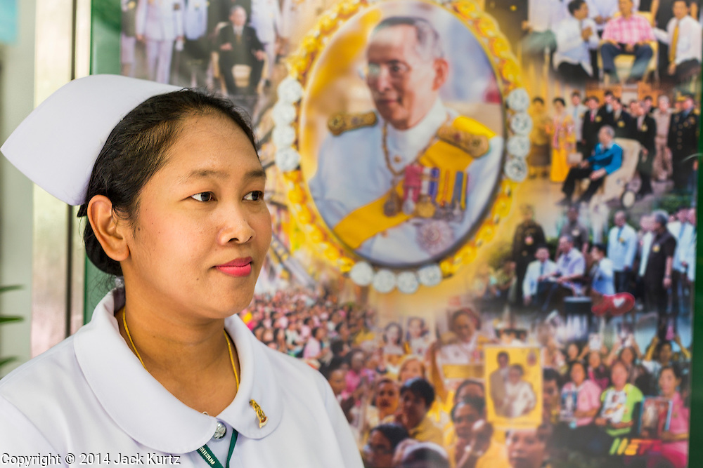 09 OCTOBER 2014 - BANGKOK, THAILAND: A nurse in the lobby of Sirirj Hospital stands in front of portrait of Bhumibol Adulyadej, the King of Thailand. The King has been hospitalized at Siriraj Hospital since Oct. 4 and underwent emergency gall bladder removal surgery Oct. 5. The King is also known as Rama IX, because he is the ninth monarch of the Chakri Dynasty. He has reigned since June 9, 1946 and is the world's longest-serving current head of state and the longest-reigning monarch in Thai history, serving for more than 68 years. He is revered by the Thai people and anytime he goes into the hospital thousands of people come to the hospital to sign get well cards.   PHOTO BY JACK KURTZ