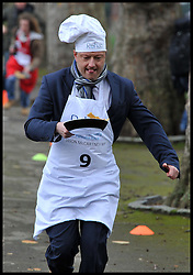 Jason McCartney MP takes part in the MP's and Lords race against political Journalist in the Rehab Parliamentary Pancake Shrove Tuesday race a charity event which sees MPs and Lords joined by media types in a race to the finish. Victoria Tower Gardens, Westminster, Tuesday February 12, 2013. Photo By Andrew Parsons / i-Images