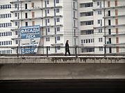 Nowosibirsk/Russische Foederation, RUS, 19.11.07: Person ueberquert eine Brücke vor einem Plattenbau im Zentrum der sibirischen Hauptstadt Nowosibirsk.<br /> <br /> Novosibirsk/Russian Federation, RUS, 19.11.07: Person walking across a bridge in front of a panel house in the center of the Siberian capital city Novosibirsk.