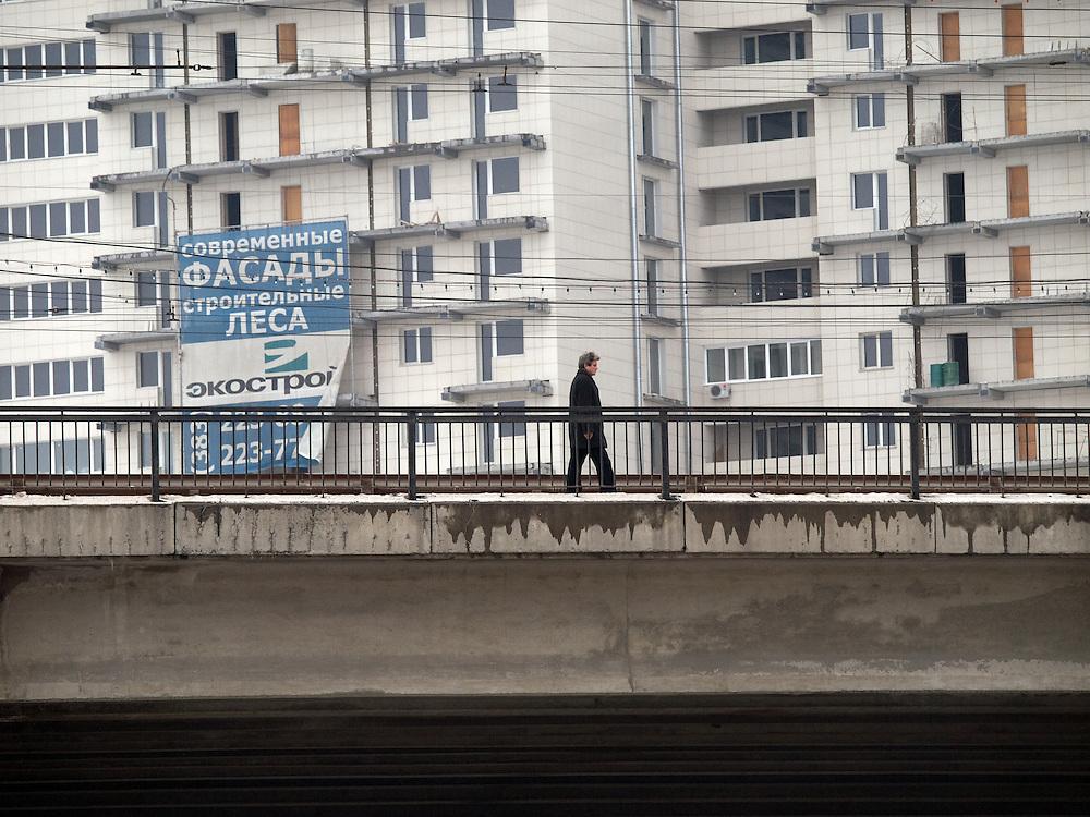 Nowosibirsk/Russische Foederation, RUS, 19.11.07: Person ueberquert eine Br&uuml;cke vor einem Plattenbau im Zentrum der sibirischen Hauptstadt Nowosibirsk.<br /> <br /> Novosibirsk/Russian Federation, RUS, 19.11.07: Person walking across a bridge in front of a panel house in the center of the Siberian capital city Novosibirsk.