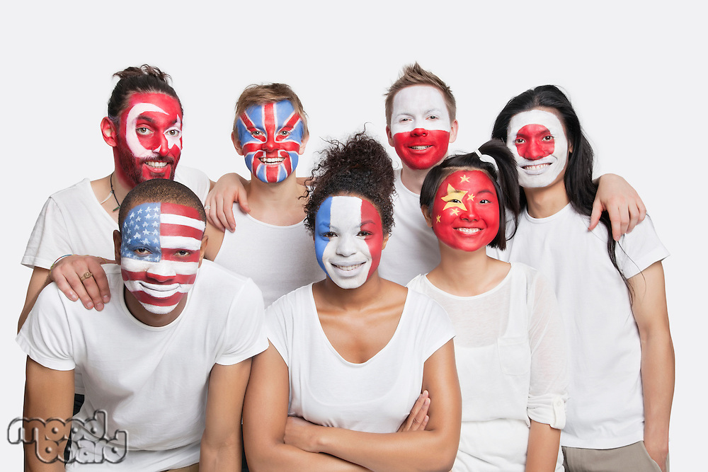 Portrait of Multi-ethnic group of friends with various national flags painted on their faces against white background