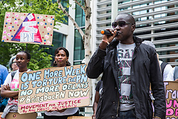 London, UK. 10 July, 2019. Larry, a refugee from Nigeria, addresses campaigners from groups including Movement for Justice and Out and Proud protesting outside the Home Office against the government department's decision to try to block the return to the UK of PN, a Ugandan lesbian removed from the UK using the now unlawful fast track procedure in 2013 but who the High Court ordered on 24th June must be returned to the UK by the Home Office after the handling of her case was ruled to be 'procedurally unfair'.