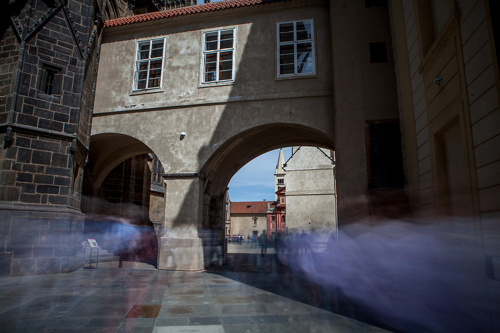 Tourist groups and visitors passing the gate of the third courtyard of Prague Castle. On the left  St. Vitus Cathedral. This cathedral is a prominent example of Gothic architecture and is the largest and most important church in the country.