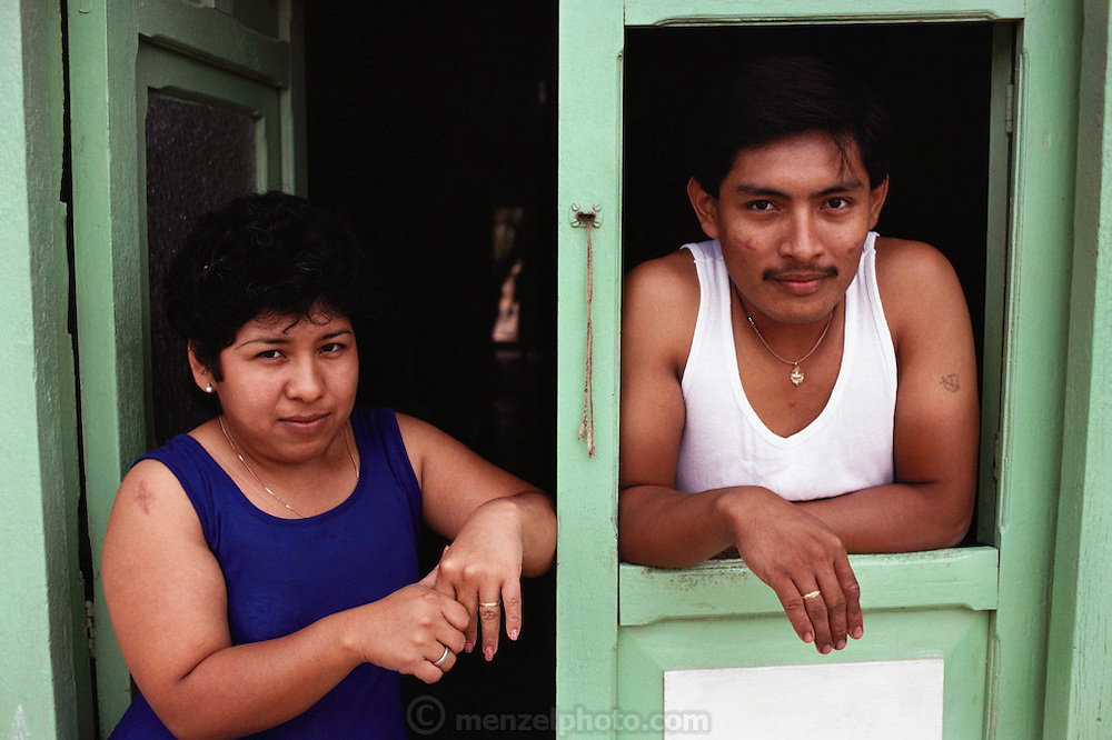 Couple looking out the front door of their pink house, Lerma Village, Yucatan, Mexico.
