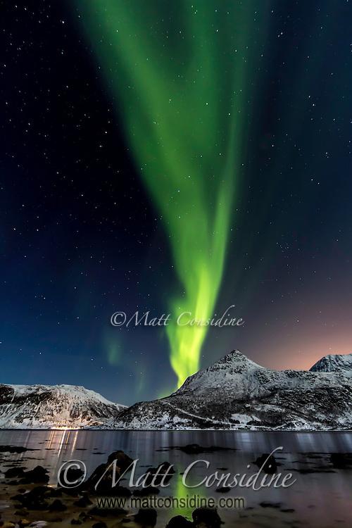 A blaze of northern lights seems to burst from the mountain. (Photo by Travel Photographer Matt Considine)