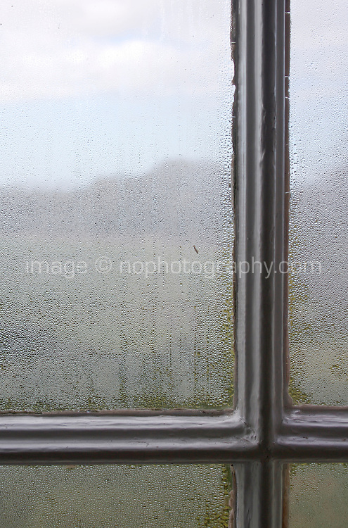 Morning condensation on sash window pane with rural landscape
