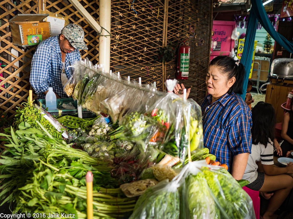 13 AUGUST 2016 - BANGKOK, THAILAND:  A produce vendor sells fresh vegetables from his cart in the Pom Mahakan slum. Residents of the slum have been told they must leave the fort and that their community will be torn down. The community is known for fireworks, fighting cocks and bird cages. Mahakan Fort was built in 1783 during the reign of Siamese King Rama I. It was one of 14 fortresses designed to protect Bangkok from foreign invaders. Only of two are remaining, the others have been torn down. A community developed in the fort when people started building houses and moving into it during the reign of King Rama V (1868-1910). The land was expropriated by Bangkok city government in 1992, but the people living in the fort refused to move. In 2004 courts ruled against the residents and said the city could take the land. Eviction notices have been posted in the community but most residents have refused to move. Residents think Bangkok city officials will start evictions around August 15, but there has not been any official word from the city.     PHOTO BY JACK KURTZ