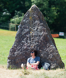 © Licensed to London News Pictures. 24/06/2015. Pilton, UK.   A festival goer at Glastonbury Festival relaxes under the shade of a stone at the Stone Circle on a sunny afternoon on  Wednesday Day 1 of the festival.        The pedestrian gates to the festival opened at 8am this morning, with many festival goers arriving and waiting throughout last night for the opening.  This years headline acts include Kanye West, The Who and Florence and the Machine, the latter having been upgraded in the bill to replace original headline act Foo Fighters.  Photo credit: Richard Isaac/LNP