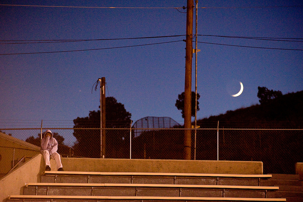 102811       Brian Leddy.A boy sits on a ledge at Public School Stadium as the moon begins to ride during Friday night's football game between Miyamura and Los Lunas.