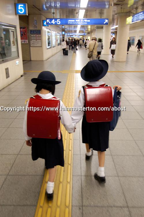 Two young Japanese girls in school  uniform walking through railway station