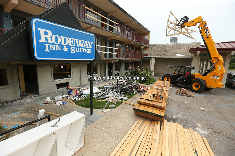 A construction worker moves prefabricated trusses on the site of the Rodeway Inn that is under renovation by owner Bruce Patel's Fusion Hospitality.
