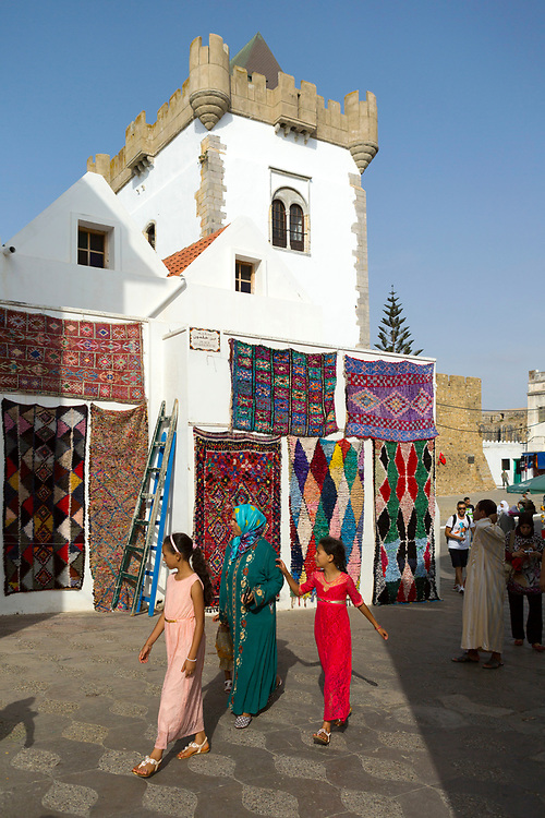 Street architecture, Asilah, Northern Morocco, 2015-08-03.<br /><br />Asilah is a sleepy fishing town in the North of Morocco, just one hour south of Tangier. While not completely off Morocco's well-beaten path, it's often missed by travellers bound inland for Fez or Chefchaouen, yet has a uniquely alluring charm. With an immaculately restored medina that's re-painted vivid shades of blue & white each summer, Asilah has the feel of being Morocco's own Santorini - a great spot to see the more chilled out, seaside town life in Morocco.  <br /><br />The town lies in the middle of a fascinating history in historical, architectural and artistic terms. It's 3,600 year old history that includes a varied range of occupiers, involving Roman, Arab Portuguese, Spanish and French colonisation. Many famous writers and artists have spent time here; in ancient times is it reported Herecules did a tour of the area and, more recently; Paul Bowles, Tennessee Williams, Edith Wharton, Jean Genet (who is buried in the nearby town of Larache), William Burroughs, Jimi Hendrix and Henri Matisse have all found the area inspiring. The Portuguese ramparts remain fully intact and a full day can be spent wandering through its old gates and the ever narrowing medina streets inside the walls.<br /><br />The architecture in Asilah has been heavily influenced by these different periods of occupation, which is one of the main reasons for its unique and characterful feel. Evidence of Mediterranean design can be seen in the rampart walls and gates themselves, reflecting the Spanish & Portuguese influence on the Asilah's development, Roman ruins can be found in the nearby town of Larache and Arab influences are more subtly found in the decorative window shutters and the labyrinth like medina layout to the streets. <br /><br />If a lover of the quirkier details found in the medinas of Morocco, then Asilah won't disappoint, with hundreds of creatively designed doorways, decorative window shutters and ret
