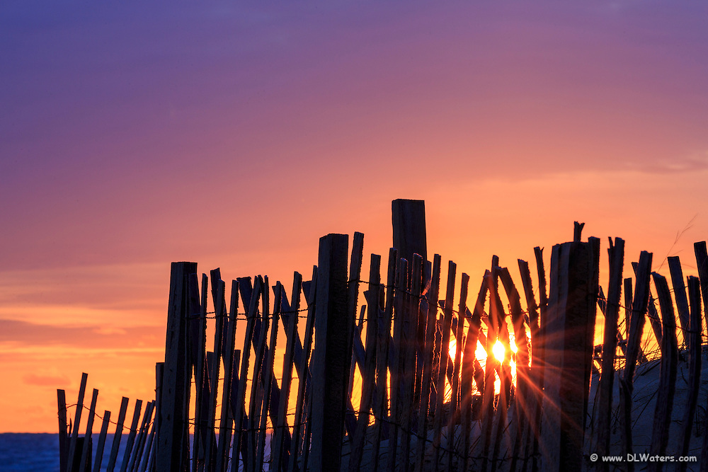 Sand fence starburst at sunrise along Kitty Hawk Beach on the Outer Banks.