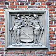 A plaque depicting two men, mirror images of each other, on the wall outside a house in historic Bruges, Belgium.
