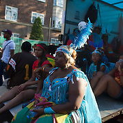 A group of tired young dancers rest on the back of truck at the end of the two day carnival.The Notting Hill Carnival has been running since 1966 and is every year attended by up to a million people. The carnival is a mix of amazing dance parades and street parties with a distinct Caribbean feel.