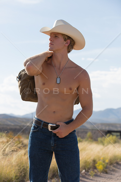 shirtless cowboy on a dirt road with a bag