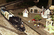 A g-scale train passes a town, on it's way through the garden.  It's part of Jack and Sharon Wilson's 'Little River Railroad' during the open garden tour for garden railroad clubs from Cincinnati, Columbus and Indianapolis, Sunday, July 15, 2007.