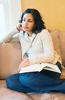 Portrait of thoughtful young woman with book.