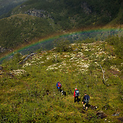 Trekkers walking under a rainbow in the Skarvheimen nature reserve in Norway
