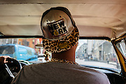 A young Cuban rides in a taxi ride through Centro Havana, where goods from the US are now regularly seen. Wearing items from the US have become a status symbol for Cubans.