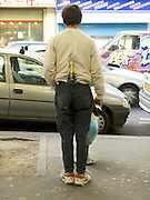 homeless person with a champagne bottle in his belt and hand