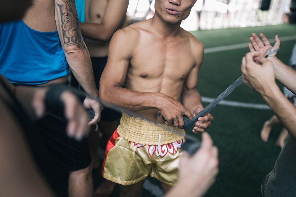 Chiang Mai, Thailand -- May 20, 2017: A trainer helps wrap a hand at the Chiangmai Muay Thai Training Center in northern Thailand.