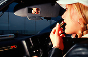 A girl applying her lipstick in a car, Girlracers, Southend, UK 2004