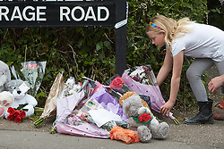 © Licensed to London News Pictures. 25/05/2015. DIDCOT, UK. A young girl leaves flowers at the scene in Vicarage Road, Didcot, where three bodies were found yesterday (Sunday). Police continue to search for Jed Allen in connection with the deaths. Photo credit : Cliff Hide/LNP