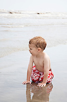Boy on hands and knees in water from sea