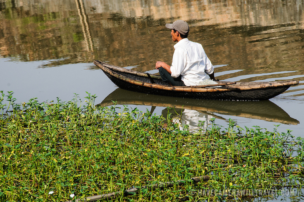 A man in a wooden canoe floats by some reeds in Hue, Vietnam.