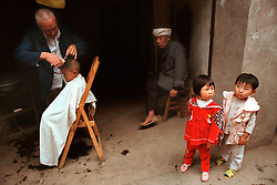 Dacheng,China.Children in a barber shop in this small town that will be flooded. ©Carmen Secanella