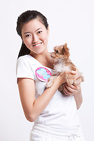 Portrait of smiling Asian woman with a puppy against white background