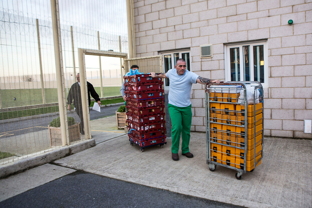 Prisoners transport food in special containers and bread crates from the main kitchen through the prison to a wing to be served.  HMP/YOI Portland, Dorset. United Kingdom.