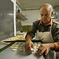 VENICE, ITALY - NOVEMBER 15:  An baker prepares biscuits at theJewsh bakery at the Ghetto on November 15, 2011 in Venice, Italy. Established in 1516 the Ghetto of Venice was the area were Jews were compelled to live during the Venetian Republic. The English term 'ghetto' is derived from the Venetian term for 'slag' and refers to the refuse left the foundry that was located on the same island. In present times the ghetto is a multi-ethnical area area seen as the cultural heart of the city, but with five synagogues remains the centre of the of Jewish community.