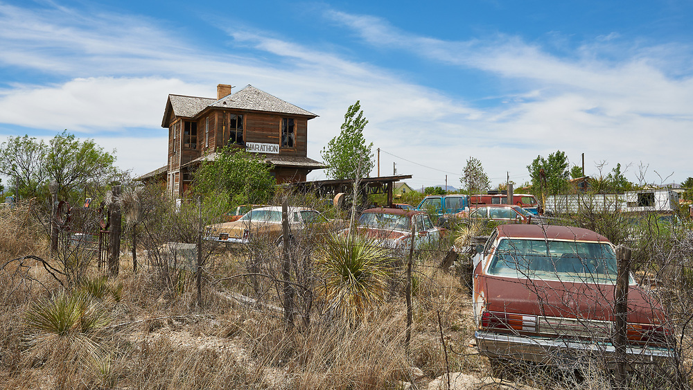 A dramatic and haggard former train depot looks out over a broad auto scrapyard in Marathon Texas. The population was 470 in 2007, after growing from 455 in 2000, but had decreased to 430 by 2010.