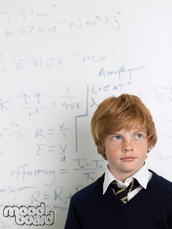 Elementary school student standing by whiteboard in math class