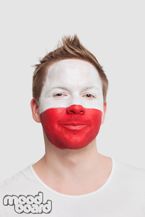 Portrait of young man with Polish flag painted on face smiling against white background