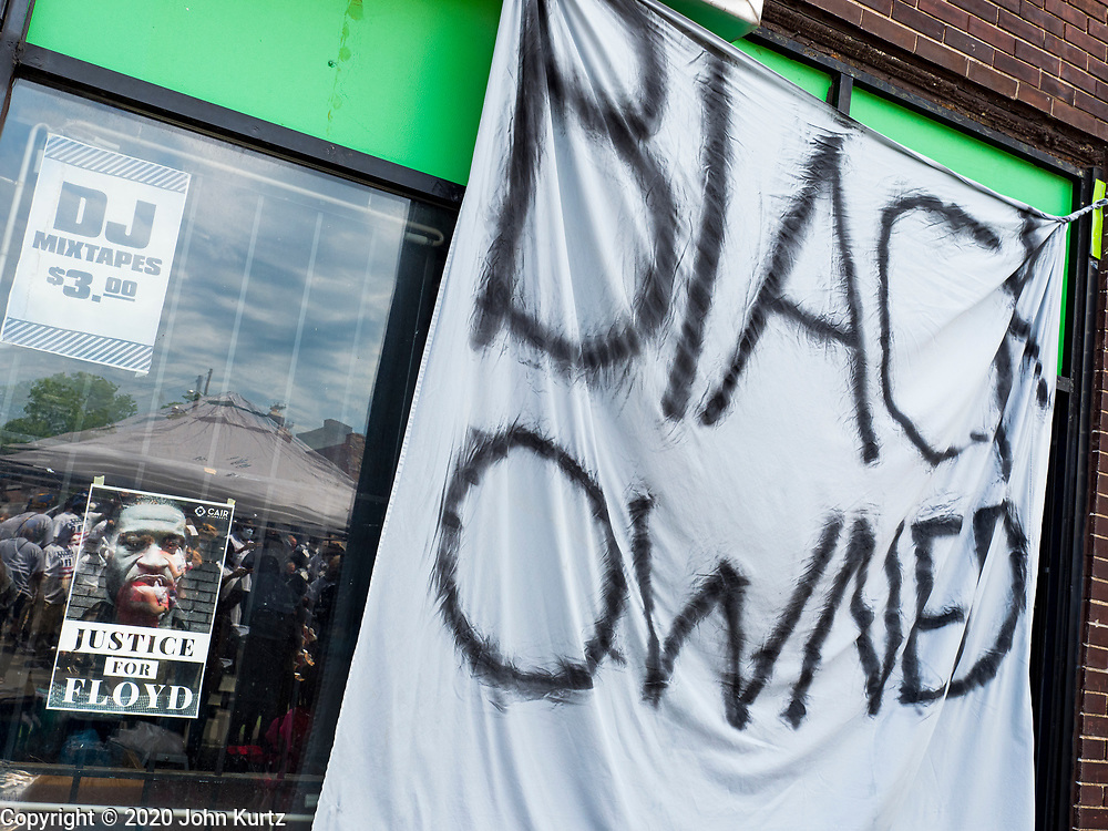 """12 JUNE 2020 - MINNEAPOLIS, MINNESOTA: The window of a Black owned business near the community memorial for George Floyd at the corner of 38th Street and Chicago Ave. in Minneapolis. The intersection is informally known as """"George Floyd Square"""" and is considered a """"police free zone."""" There are memorials to honor Black people killed by police and people providing free food at the intersection. Floyd, an unarmed Black man, was killed by Minneapolis police on May 25 when an officer kneeled on his neck for 8 minutes and 46 seconds. Floyd's death sparked weeks of ongoing protests and uprisings against police violence around the world.          PHOTO BY JACK KURTZ"""