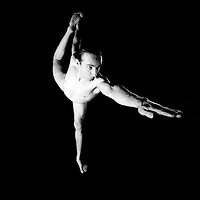 Yogi Marc Linton performs yoga poses on black backdrop