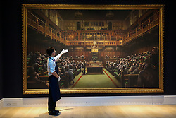 "© Licensed to London News Pictures. 27/09/2019. London, UK. A technician points at 'Banksy's artwork titled ""Dystopian View of The House of Commons Comes to London"" Est -£1.5 – £2 million during the preview of Sotheby's Frieze Week Contemporary Art Sale. The auction will take place on 3rd October 2019.  Photo credit: Dinendra Haria/LNP"