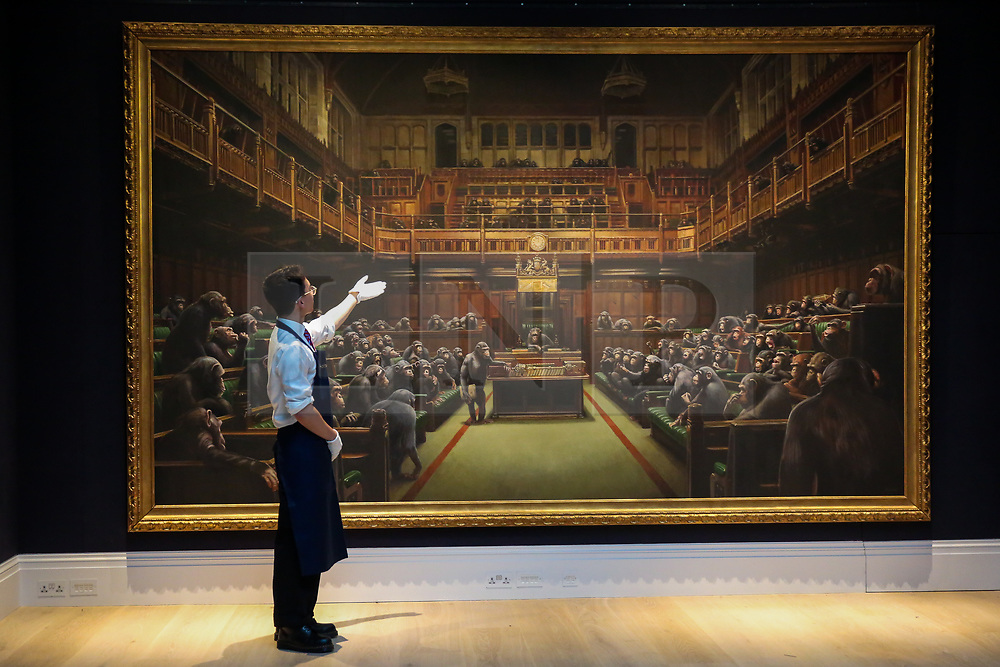 """© Licensed to London News Pictures. 27/09/2019. London, UK. A technician points at 'Banksy's artwork titled """"Dystopian View of The House of Commons Comes to London"""" Est -£1.5 – £2 million during the preview of Sotheby's Frieze Week Contemporary Art Sale. The auction will take place on 3rd October 2019.  Photo credit: Dinendra Haria/LNP"""