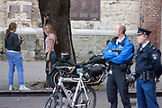 Agenten kijken toe hoe een meisje poseert voor een ander meisje op het Domplein in Utrecht.<br /> <br /> A policeman is watching while a girl is posing at the Domplein in Utrecht.