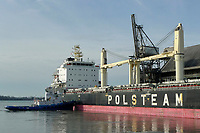 Tug pushing bulk ship into wharf to deliver raw sugar cane, Redpath sugar refinery, Toronto , Ontario, Canada