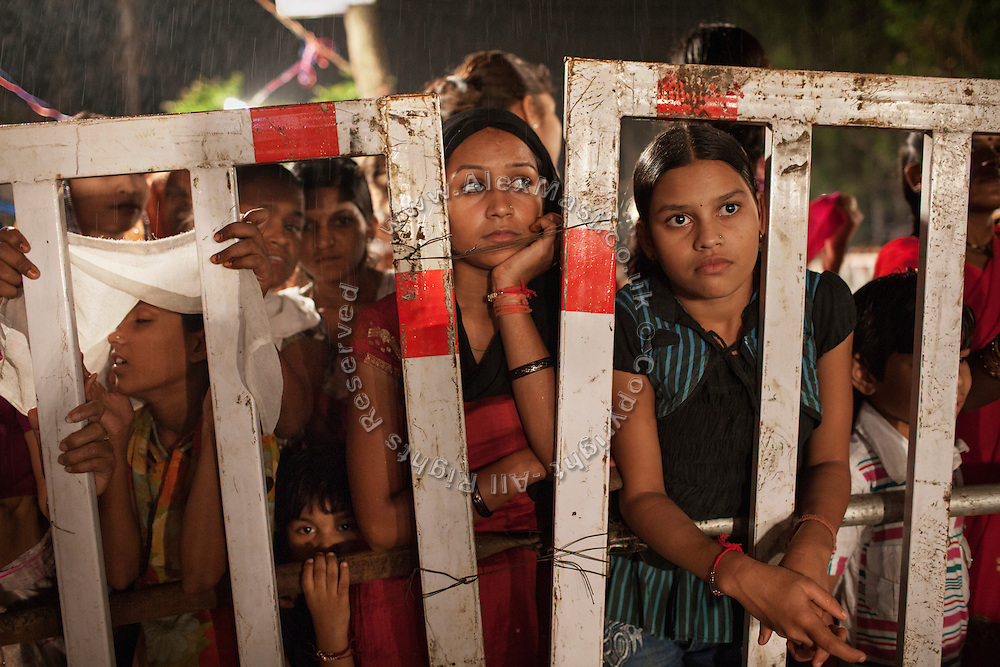 Under heavy rain, a group of young women is observing the  celebrations for the festival of Janamashtami, the birthday of Hindu God Krishna, in Bhopal, Madhya Pradesh, India, near the abandoned Union Carbide (now DOW Chemical) industrial complex.