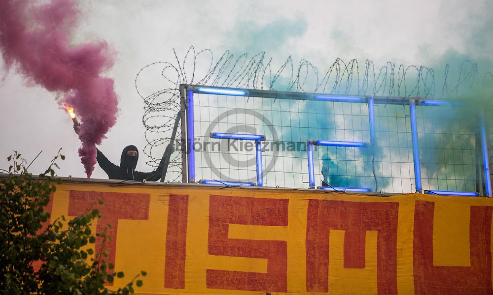 Hamburg, Germany - 05.07.2017<br /> <br /> A demonstrator with fog pyrotechnics on the roof of the left center &rdquo;Rote Flora&rdquo;. Anti-G20 rave under the slogan &rdquo;Lieber tanz ich als G20&rdquo; (&quot;I prefer to dance instead of G20&rdquo;) moves through Hamburg. According to police, about 12,000 people are involved, according to the organizers more than 25,000 people participate.<br /> <br /> Ein Demonstrant mit Nebelkerzen auf dem Dach des linken Zentrums &quot;Roten Flora&quot;. Anti-G20 Nachttanz-Demo unter dem Motto &rdquo;Lieber tanz ich als G20&rdquo; zieht durch Hamburg. Laut Polizei beteiligen sich etwa 12.000 Personen, laut den Veranstaltern nehmen mehr als 25.000 Menschen teil. <br /> <br /> Photo: Bjoern Kietzmann