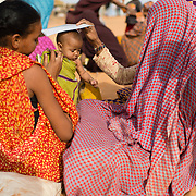 Two women shade a baby with a refugee registration card while waiting in a food distribution queue at the Mbera refugee camp for Malian refugees in Mauritania on 1 March 2013.