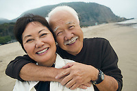 Mature couple embracing on beach (close-up) (portrait)