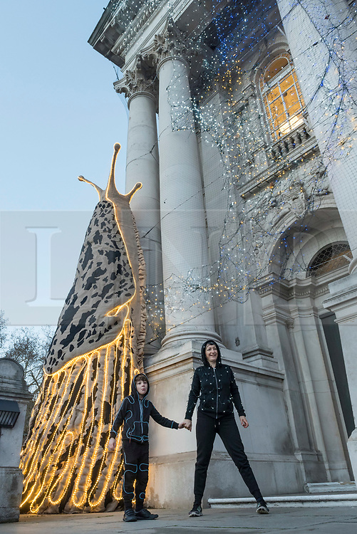 """© Licensed to London News Pictures. 30/11/2018. LONDON, UK. Turner Prize nominated artist Monster Chetwynd and son Dragon pose in front of her new Tate Britain Winter Commission.  The artist, formerly known as """"Marvin Gaye"""" and """"Spartacus"""", has transformed Tate Britain's iconic Neo-Classical façade to mark the winter season with a new piece inspired by the winter solstice, involving a dazzling light display and elements of sculpture.  Winter Commission 2018: Monster Chetwynd will be switched on daily from 1st December 2018 - 28 February 2019.  Photo credit: Stephen Chung/LNP"""