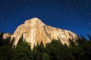 El Capitan under a starry moonlit night (climber's headlamps visible), Yosemite National Park, California USA